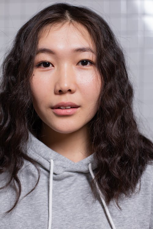 Delighted young ethnic female model looking at camera in studio