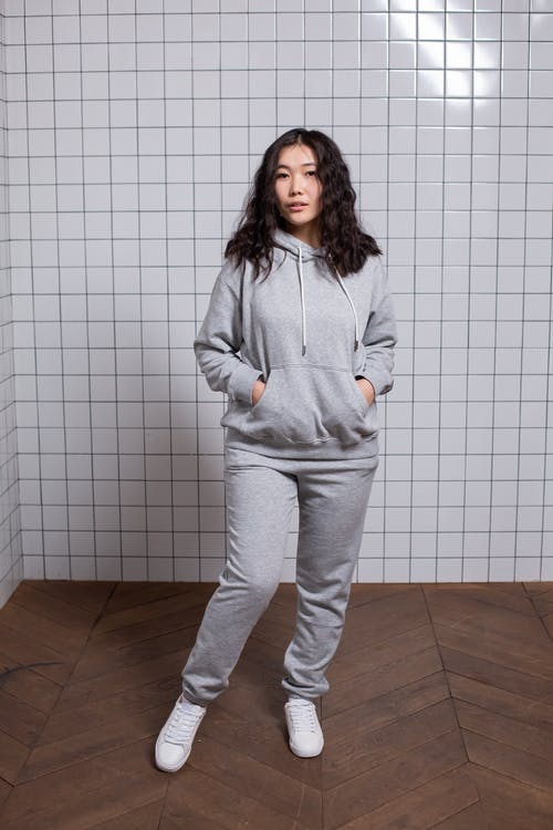 Full body of trendy young Asian lady in stylish comfy clothes standing against tile wall with hands in pocket and looking at camera