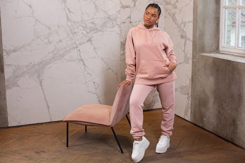 Confident black woman in sportswear in room