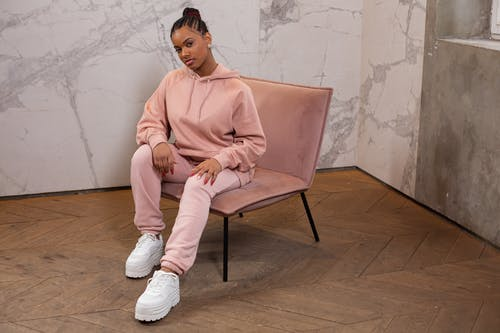 Full body of trendy African American female wearing stylish hoodie and pants looking at camera while sitting on armchair against wall