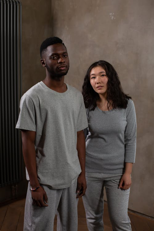 Young Asian woman and black man in gray sportswear looking at camera in modern studio
