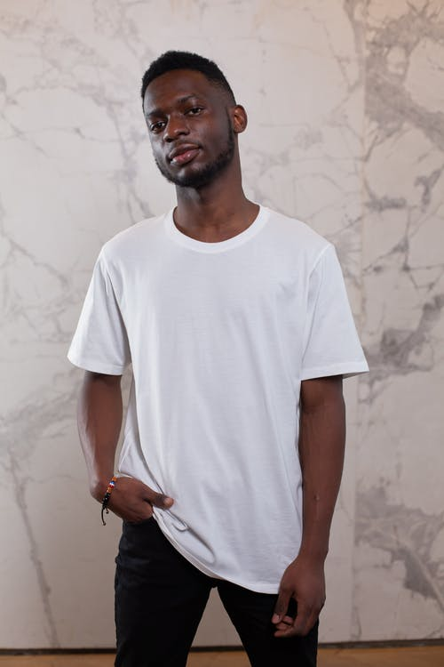 Young confident African American male in simple white shirt looking at camera near wall with abstract patterns