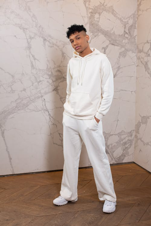Full body of serious African American male with hands in pockets wearing white sports suit looking at camera