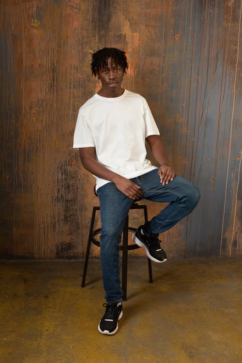 Full body of self assured young African American male model with dreadlocks in casual white t shirt and jeans sitting on chair and looking at camera against wooden wall