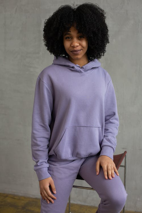 Positive young African American female model with dark curly hair wearing trendy hoodie sitting on chair and looking at camera against gray background
