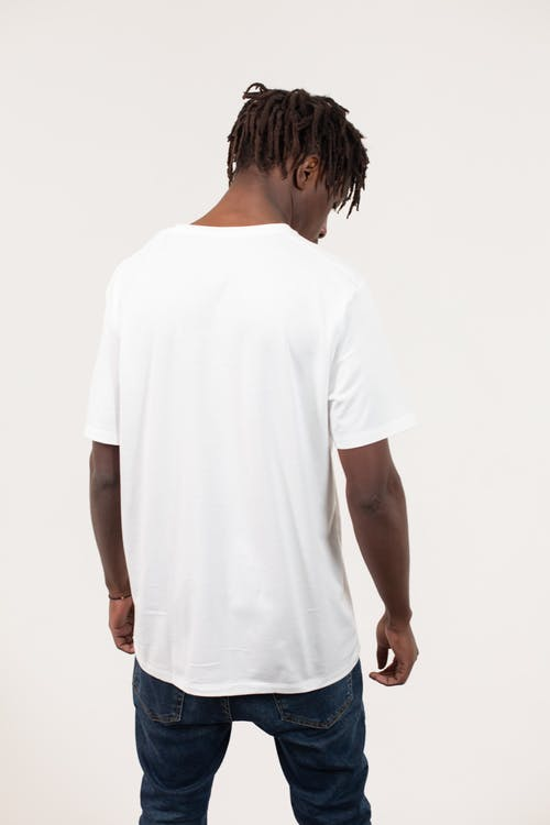 Back view of anonymous young informal black guy with Afro dreadlocks in casual outfit standing against white background and looking down