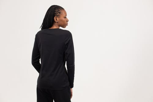 Back view of self assured young ethnic lady with Afro braids in total black outfit standing against white background and looking away