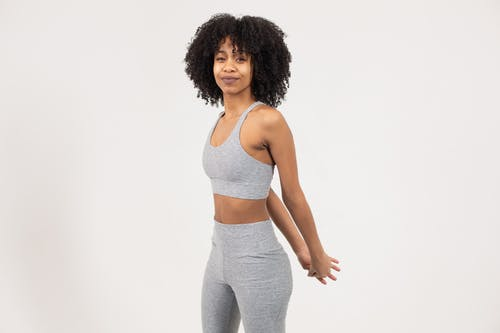 Fit young black female athlete stretching arms before workout