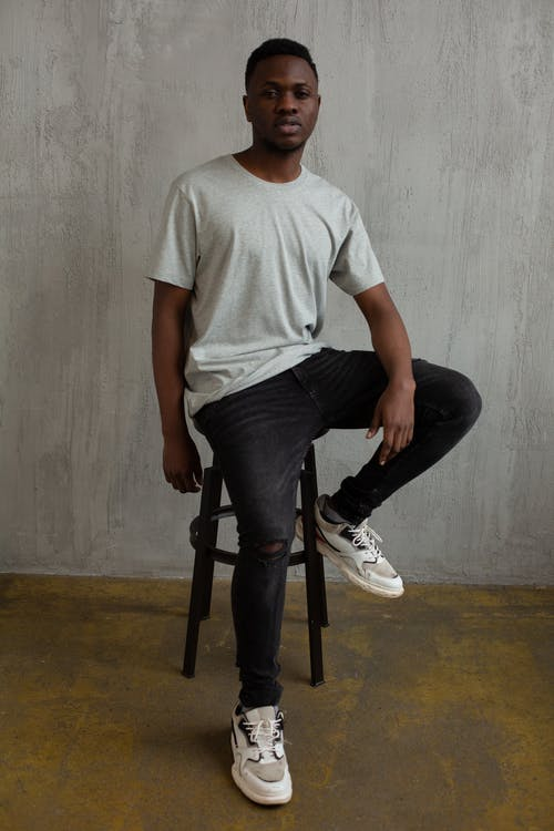 Full body of fashionable young African American guy in stylish casual outfit sitting on stool and looking at camera in studio