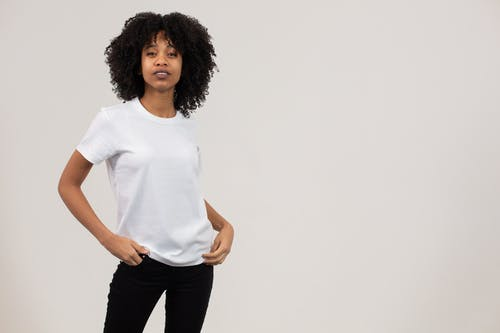 Self esteem young black female model with dark Afro hair in white t shirt standing in light studio with hands in pockets and looking at camera