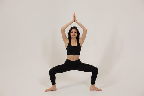 Fit young ethnic woman standing in Goddess asana during yoga lesson