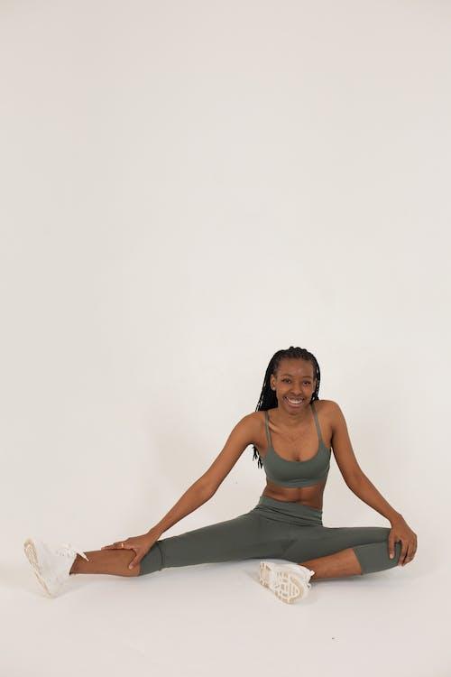 Cheerful African American sportswoman on activewear in studio