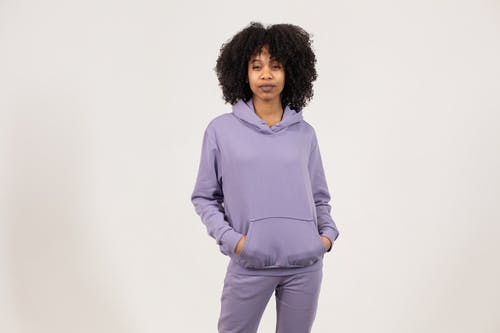 Serious African American female with curly hair wearing trendy clothes standing with hands in pocket and looking at camera against white background