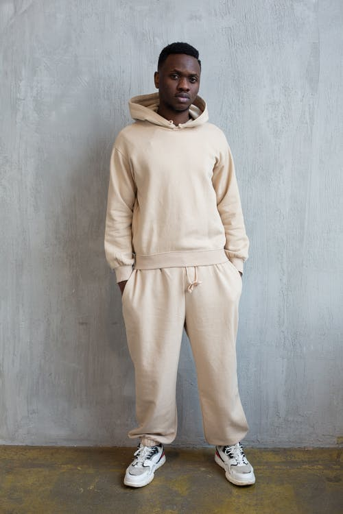 Full length confident African American male wearing light comfortable hoodie and pants standing with hands in pockets in studio and looking at camera calmly