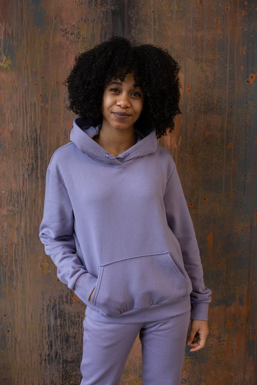 Content black woman in comfy sportswear standing in studio