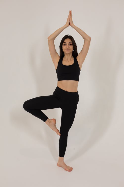 Full body slim positive ethnic female in black sports bra and leggings performing Tree Pose in light studio and looking at camera