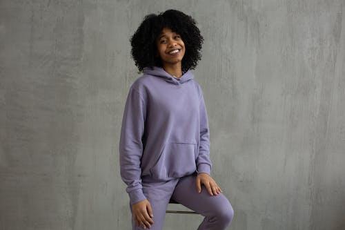 Smiling black woman in hooded sweatshirt sitting on high chair