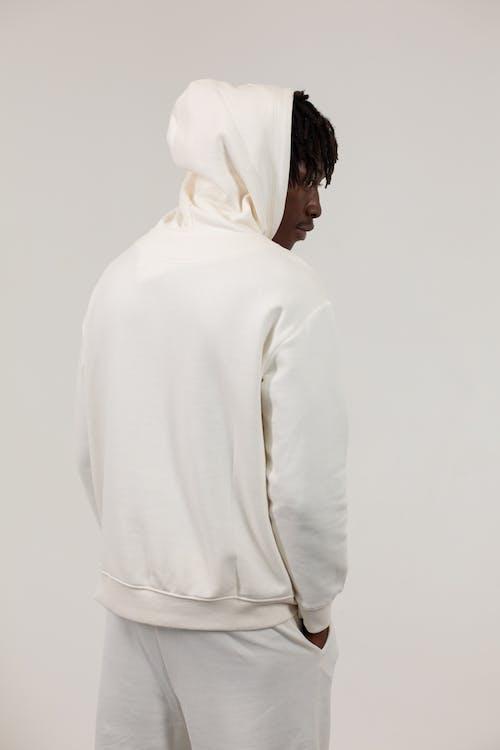 Serious black man in white hooded sportswear against light background