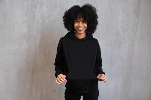 Kobieta W Czarnej Koszuli Z Długim Rękawem I Czarnych Spodniach Stojąca Obok Szarej ściany