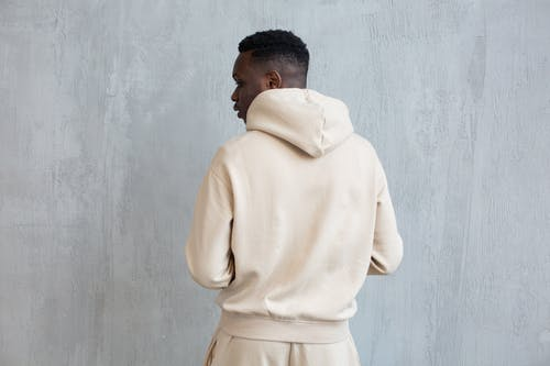 Back view of African American male wearing white hoodie and pants while standing near gray wall in light place
