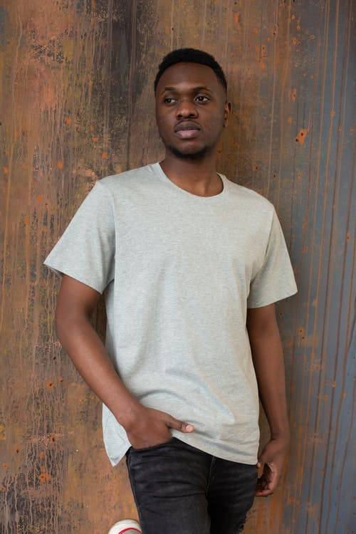 Pensive young black male in casual clothes standing near brown wooden wall in light place and looking away