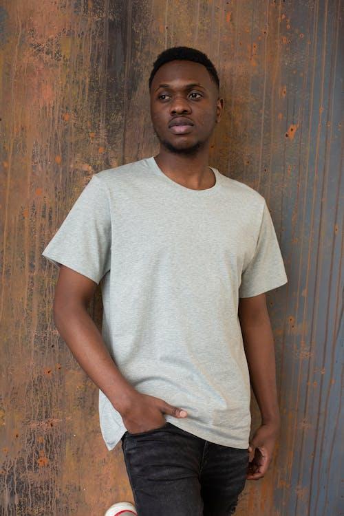 Мужчина в белой футболке с круглым вырезом стоит у коричневой деревянной стены
