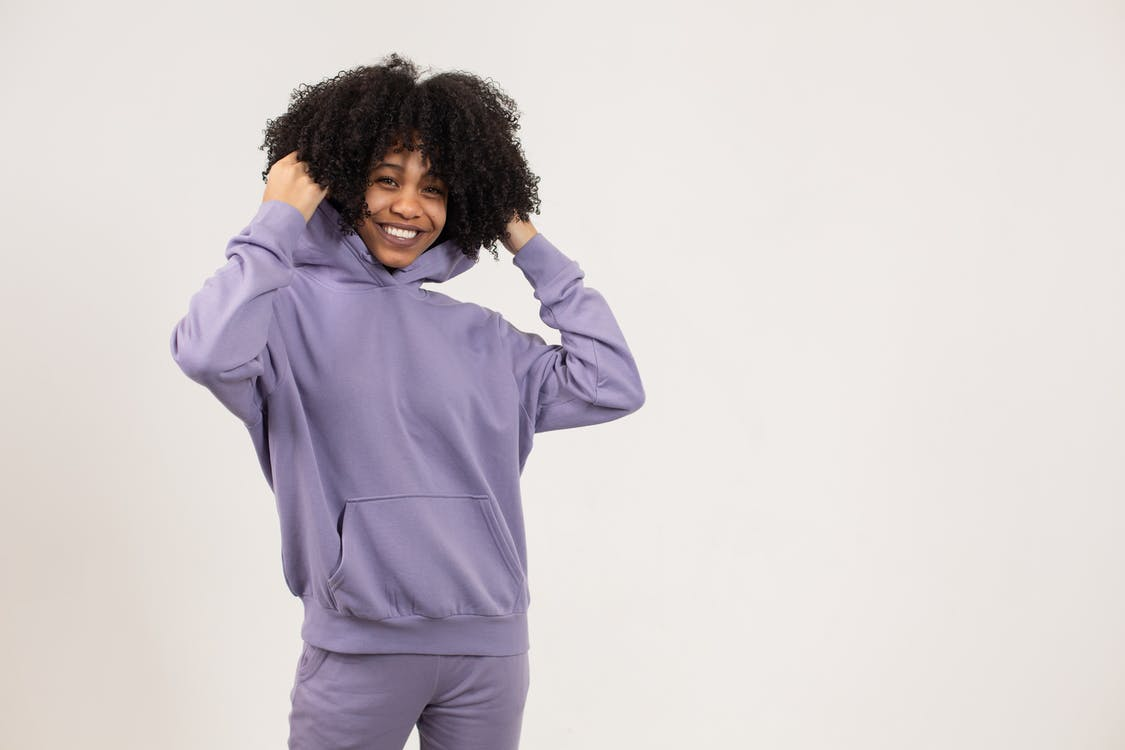 Positive young African American female in purple hoodie and pants standing in light studio on white background and looking at camera