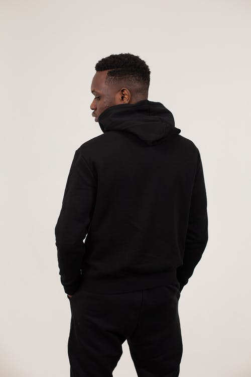Back view of serious African American male wearing black sportive outfit standing with hands in pockets against white background and looking down