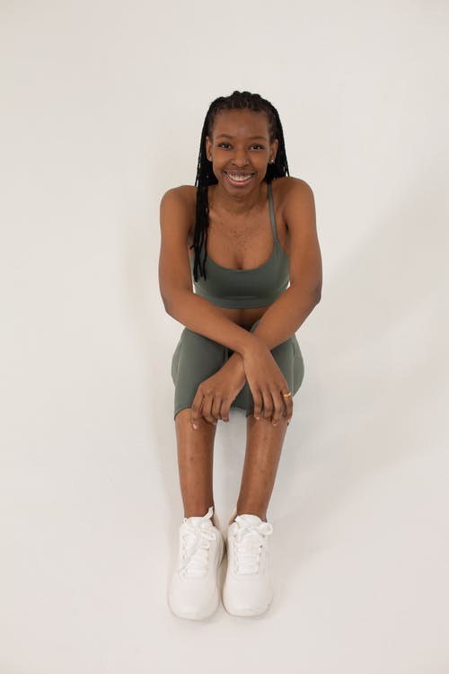 High angle full body of positive African American female model wearing sportswear and sneakers sitting with crossed arms and looking at camera