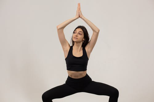 Fit female athlete in sportswear doing plie squat with namaste gesture above head against white background