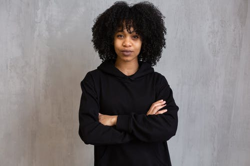 Young African American female with Afro hairstyle wearing casual clothes standing with crossed arms and looking at camera