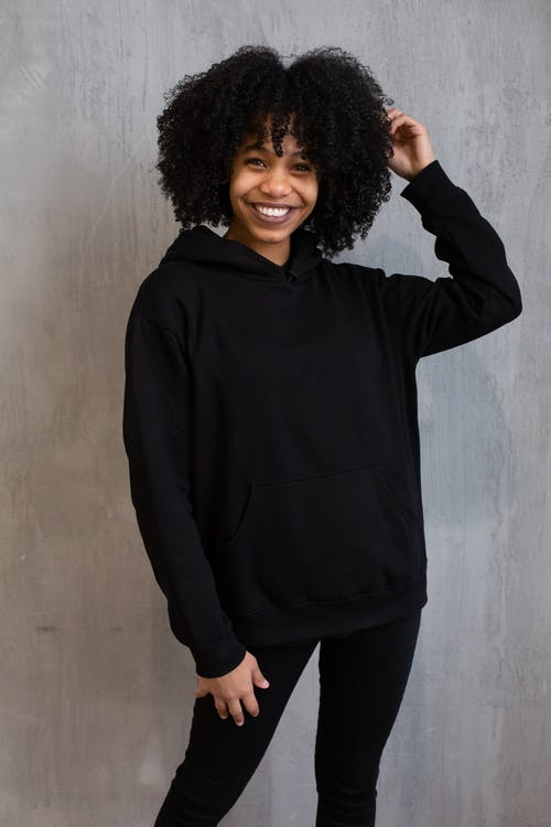 Positive African American female with curly hair wearing black hoodie and leggings and looking at camera