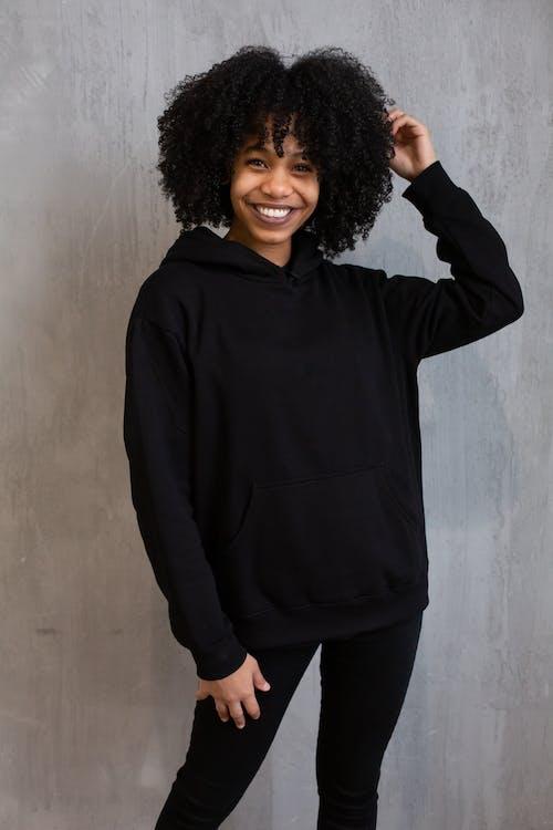 黑色拉链外套站在白墙旁边的女人