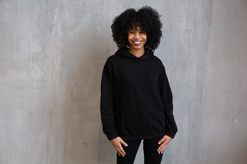 Positive African American female with Afro hairstyle wearing hoodie and leggings looking at camera