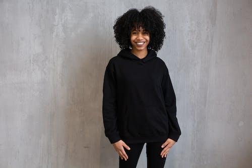 Mujer En Camisa De Manga Larga De Cuello Alto Negro De Pie Junto A La Pared De Hormigón Gris