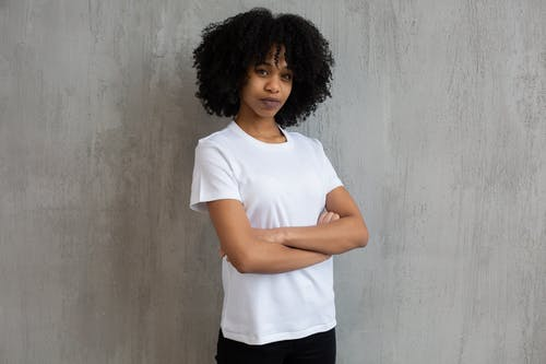 Black woman with Afro hairstyle standing with folded arms