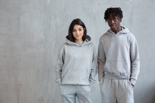 Smiling diverse man and woman wearing similar sports suits standing with hands in pockets and looking at camera