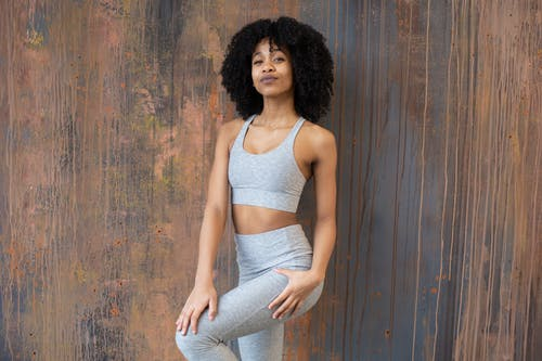 Charming fit African American female with Afro hairdo wearing sportswear standing against wooden wall and looking at camera