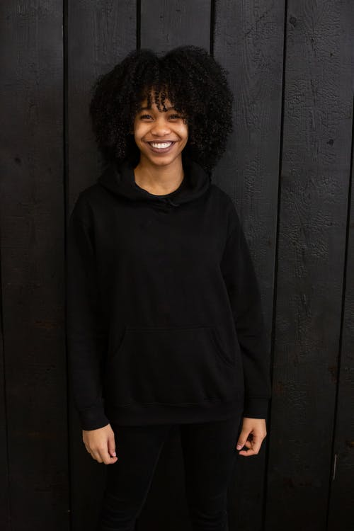 Cheerful African American female with curly hair and toothy smile wearing hoodie and leggings standing against black wooden wall