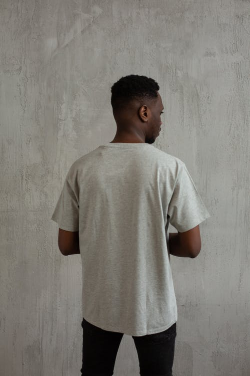 Black man in t shirt and pants in studio