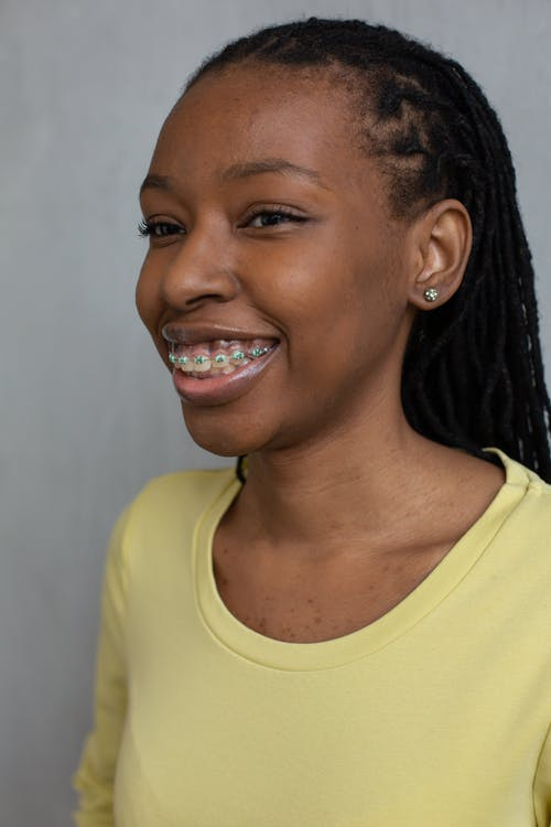Cheerful African American female with braces on teeth smiling happily and looking away against gray background