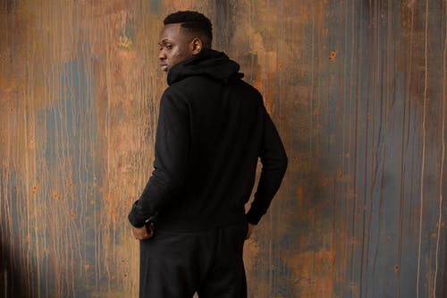 Side view of confident African American male in trendy black hoodie standing near wooden wall with hands in pockets in studio