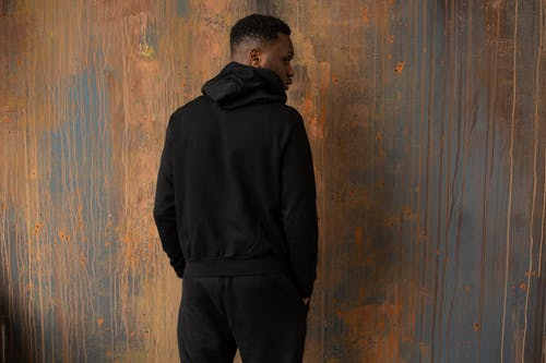 Back view of unrecognizable African American male wearing trendy black outfit standing near wooden wall with hands in pockets in room