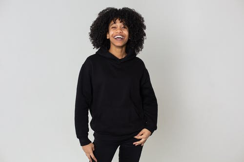 Cheerful African American female with Afro hairstyle wearing trendy black outfit smiling and looking at camera on white background in studio