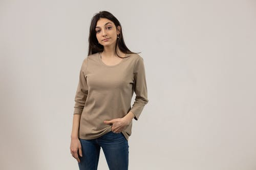 Content female wearing casual outfit and jeans looking away while standing on gray background with hand in pocket in studio