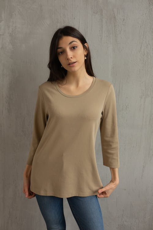 Stylish woman in beige blouse before gray wall