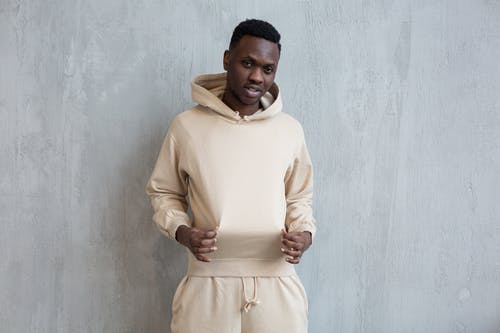 Confident African American guy standing against gray wall and holding hoodie with fingers while looking at camera