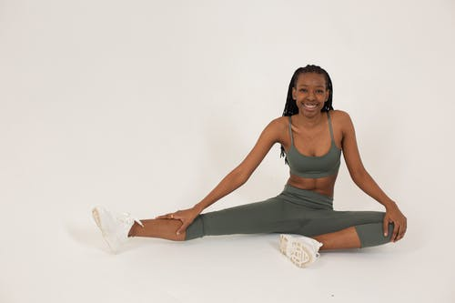 Full length of young slim African American female in gray sportswear looking at camera and smiling while stretching legs on floor