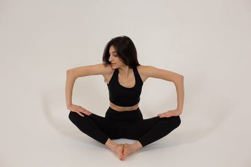Fit woman sitting in butterfly pose and pressing on legs