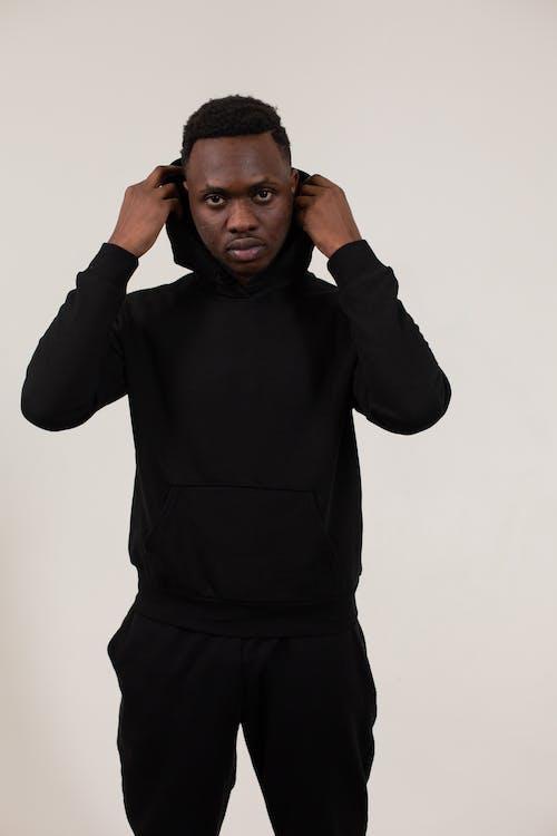 Black man putting on hood in studio